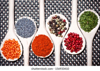 Colorful mix of assortment spices with bean seeds, poppy seeds and different types of pepper