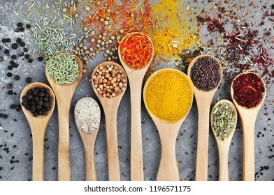 Colorful mix of herb and spice varieties: curry, coriander, turmeric, cumin, paprika, pepper, mustard, salt, thyme, cardamon, oregano, saffron, cinnamon; food ingridients background