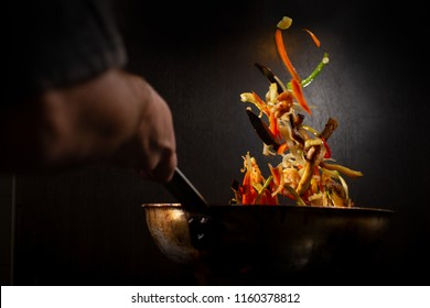 Colorful mix of vegetables being cook in a wok pan in a dark environment,  while the chef is throwing them up.