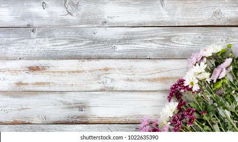 Colorful mixed flowers in bottom right corner on white weathered wooden boards