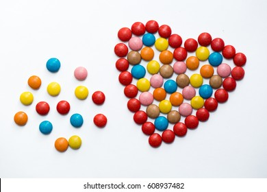 Colorful m&m button chocolate candies in the love shape on white background.