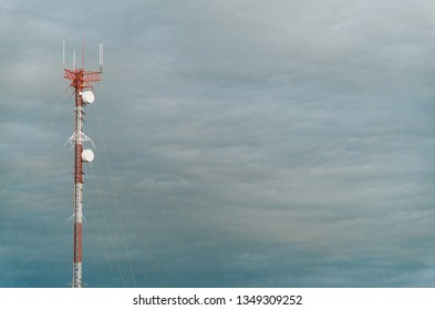 Colorful mobile phone network telecommunication tower against blue sky background. Concept of telecom, telco, connectivity, and technology