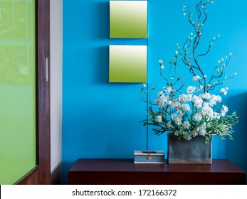 Colorful modern interior wall decorate with artificial flowers in ceramic vase
