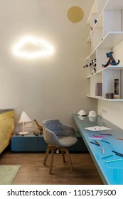 Colorful modern kid's room with white walls and a parquet with a carpet on a floor. There is a blue tabletop with pencils and caps, white shelves with toys and books, chair, luminous fancy cloud lamp.