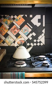Colorful mosaic tile backsplash of antique stove with kettle in luxurious French chateau castle kitchen