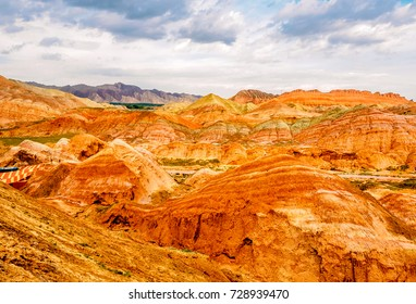 The colorful mountain with blur view of small green bushes, and blur view of mountain from afar of the Zhangye Danxia Geological Park in Gansu, China