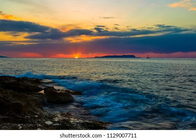 Colorful mountain silhouette and ancient ship against bright orange sun, hidden behind blue clouds, sea in foreground. Gunung Agung mountain on sunset