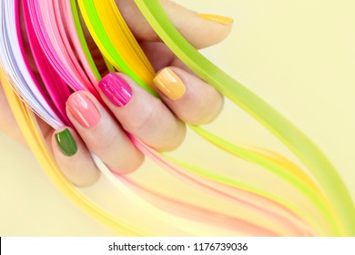 Colorful multi-colored manicure on short nails on background.Nail art.Pink, green ,yellow, peach nail Polish.