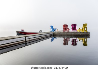 Colorful Muskoka Chairs Arranged on a Dock with a Small Motorboat on a Misty Morning - Haliburton, Ontario, Canada