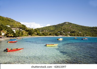 colorful native made wood fishing boats on friendship bay with mountains and tropical landscape bequia st. vincent and the grenadines in the caribbean sea