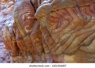 Colorful nature pattern painted on the rock wall in narrow canyon in Jordan. Pattern on the rocks, created by nature.