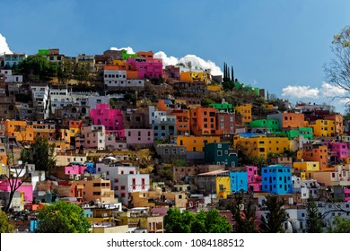 Colorful neighborhood perched on a hill with sky and cloud background in the beautiful, historic city of Guanajuato, Gto., Mexico