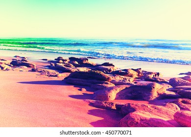 Colorful neon landscape of waves, rocks and boulders on a beach. Filtered image.