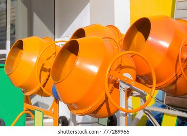 Colorful new orange cement mixers in street market. Closeup. Selective focus.