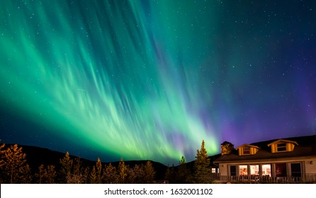 colorful night sky aurora over lodge in alaska denali national park, focus on night sky and stars