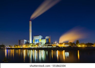 Farbige nächtliche Sicht auf eine moderne Müllverbrennungsanlage in Oberhausen, Deutschland mit tiefblauem Himmel.