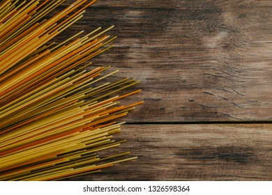 Colorful noodles on the wooden background. Top view, copy space