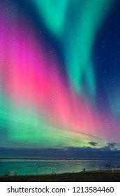 colorful northern light aurora borealis with purple, red, green and blu flames over the sky in iceland  in a beach