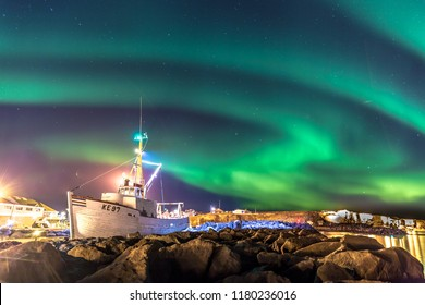 Colorful northern lights (Aurora borealis) with a boat in the foreground in Iceland
