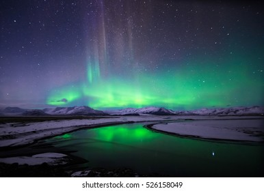 Colorful Northern lights (Aurora Borealis) and starry sky reflected over glacial lake and snow-covered mountains in Iceland.