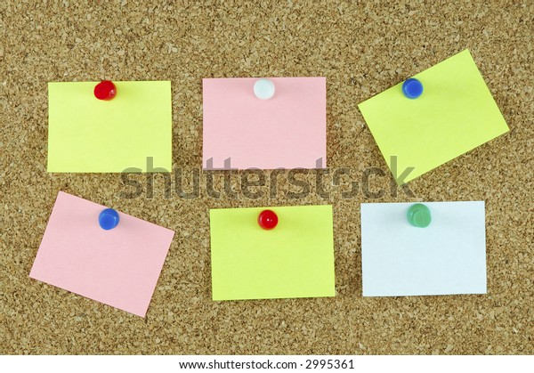 Colorful note paper  with pushpins on corkboard.