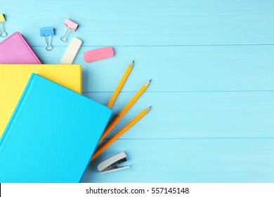 Colorful notebooks and office supplies on wooden background