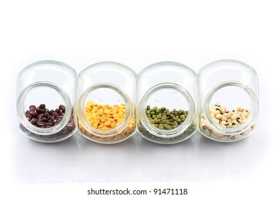 Colorful nuts in transparent glass storage. Isolated white background.