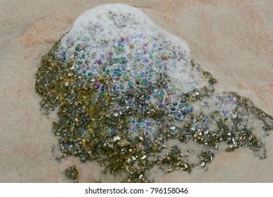 Colorful ocean foam bubbles on a rock