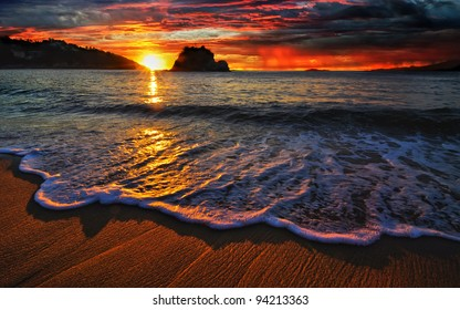 Colorful ocean sunrise with breaking wave