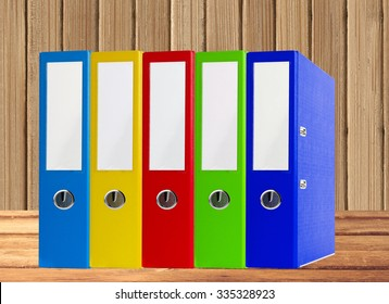Colorful office folders on wooden table over wooden background