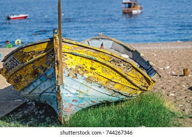 Colorful old fishing boat on a sea shore with cracked paint