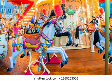 Colorful Old French carousel in a holiday park. Merry-go-round with horses
