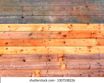 colorful old rustic wooden plank wall or floor with some of the boards stained in faded blue and reds made of reused timber