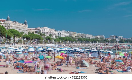 Colorful old town buildings and beach in Cannes timelapse on french Riviera in a beautiful summer day, France. Azur sea, people on sand