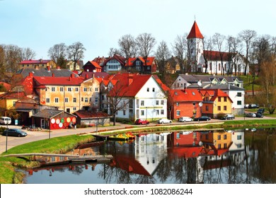 Colorful old town houses and church with lake reflection in spring morning in Talsi Latvia.