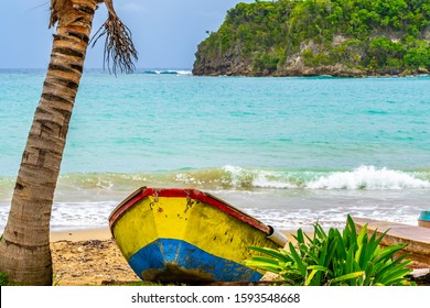 Colorful old wooden fishing boat docked under tree by water on a beautiful beach coast. White sand sea shore landscape on tropical Caribbean island. Holiday weekend summer vacation setting in Jamaica.