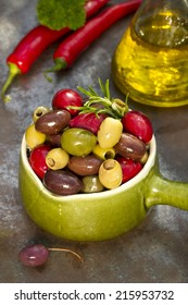 Colorful olives in a rustic bowl with olive oli and red paper on a dark background