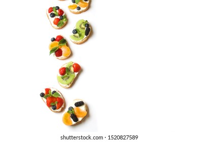 Colorful Open Sandwiches With Fresh Fruits, Berries, Cream Cheese Isolated On White. Vegetarian Healthy Diet Food. Flat Lay With Copy Space.