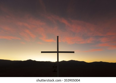 Colorful orange sunset with the silhouette of a Christian cross located at the top of a mountain at 4500m. Altiplanos, Bolivia.
