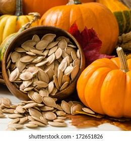 Colorful orange and yellow pumpkins and gourds surround a wooden bowl overflowing with toasted pumpkin seeds