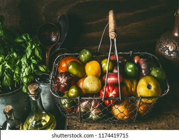 Colorful organic tomatoes in harvest basket on dark rustic kitchen table with cooking ingredients. Healthy food concept