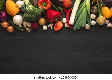Colorful organic vegetables border on dark wooden background. Healthy natural food on rustic table. Grocery shop assortment, fresh cooking ingredients top view