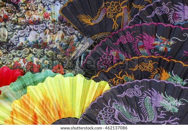 Colorful oriental hand fans in an outdoor market.