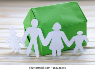 colorful origami paper house with human family