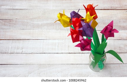 colorful origami tulip flowers bouquet in glass vase on white wooden table, international women's day background