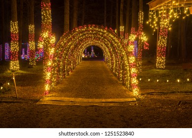 Colorful outdoor Christmas Holiday Light display with candy canes and brightly lit tunnel.