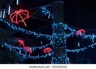 Colorful outdoor Christmas Holiday Light display with blue lights and red umbrellas.
