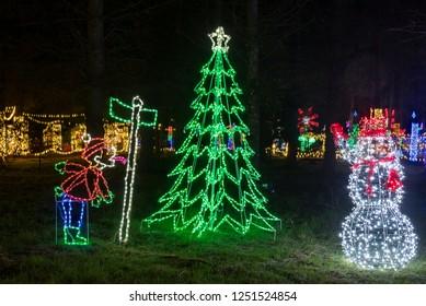 Colorful outdoor Christmas Holiday Light display with snowman and Christmas Tree.