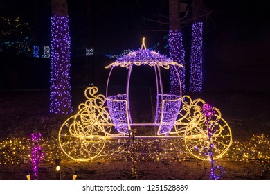 Colorful outdoor Christmas Holiday Light display with brightly lit purple and gold antique carriage.