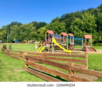 A colorful outdoor playground stands empty behind a wooden fence in Rzeszow, Poland.